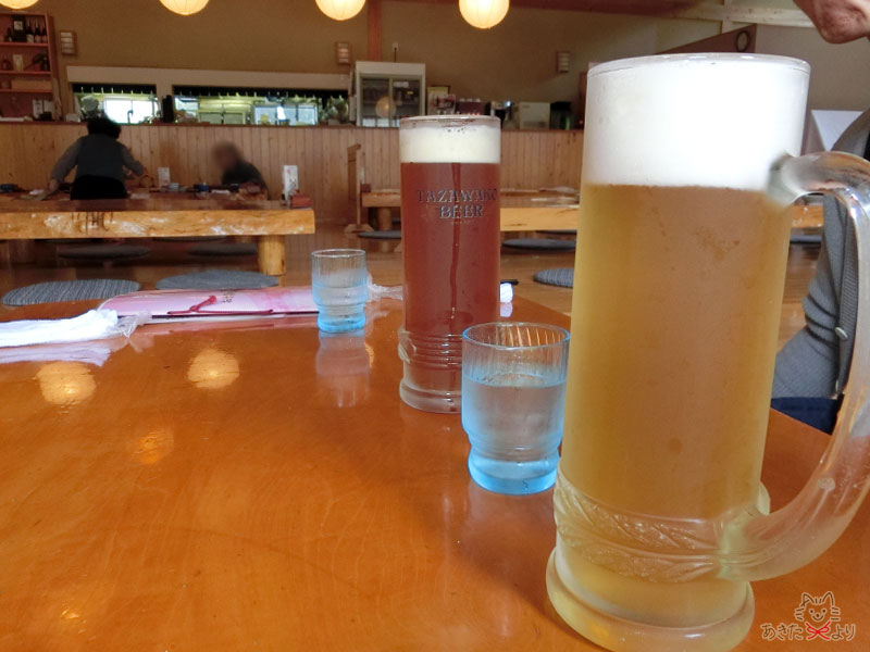 木のぬくもりあふれる落ち着いた店内、テーブルには田沢湖ビールが入った大きいジョッキがおいてある。
