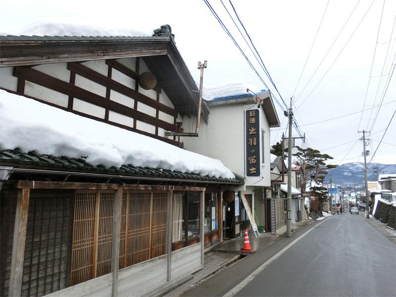 出羽の富士を作っている佐藤酒造店とその前の坂道から見える雪化粧が施された山々。