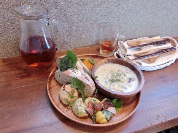 木の器に盛りつけられた豆乳のシチューとベジバーグのパンランチ
