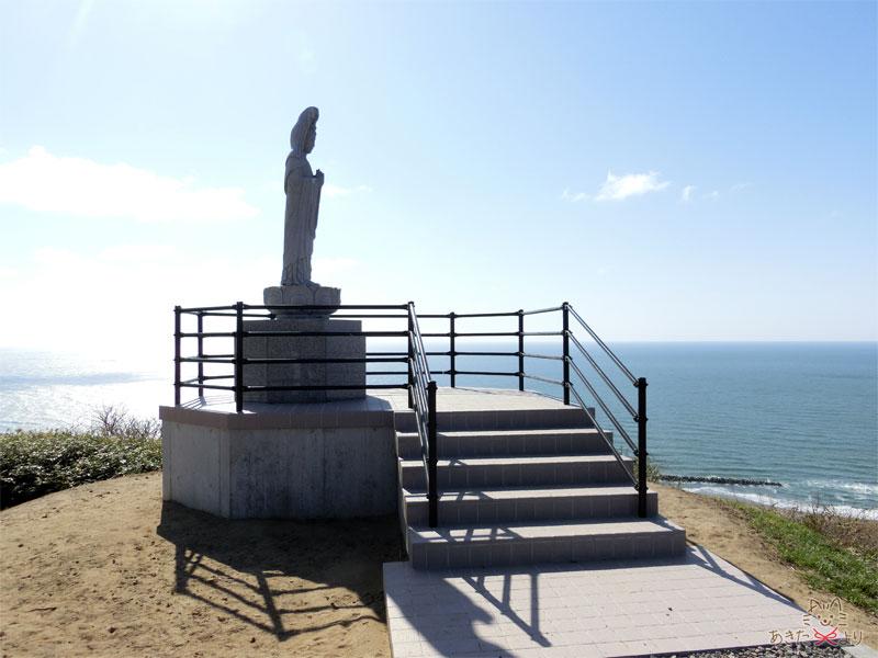 青空の元、日本海を一望する場所に立つ観音様(海難慰霊塔)