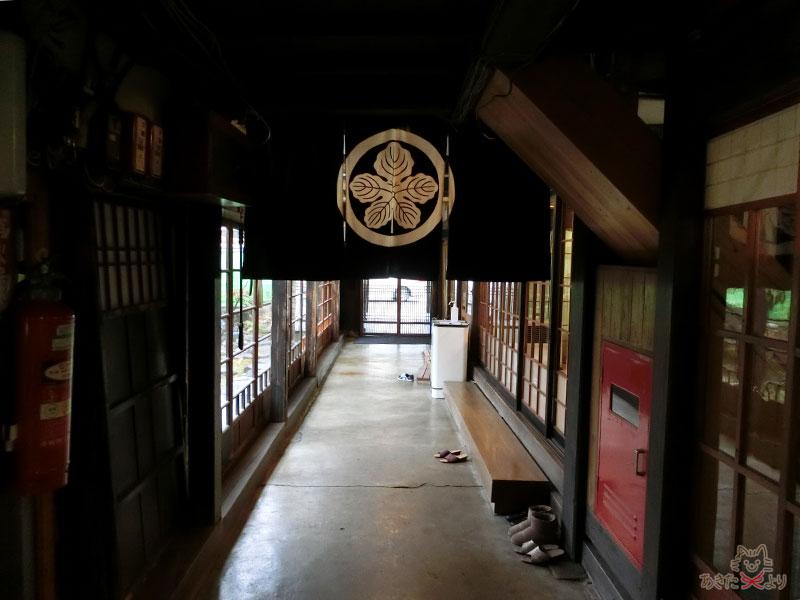 土間の廊下。少し奥に進んだところから入り口を振り返って撮った写真で、奥が入り口、左側に庭