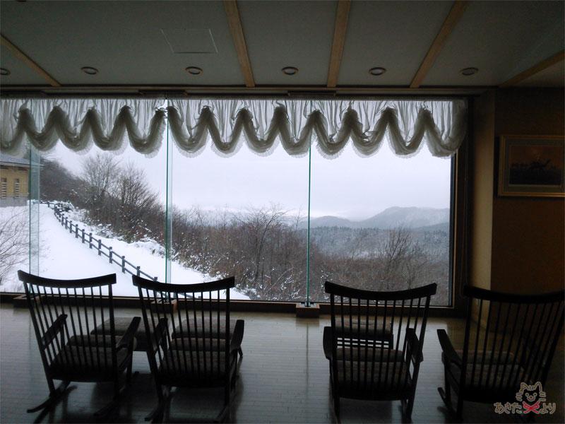 ホテルグランド天空のロビーのロッキングチェア、奥はガラス越しに田沢湖と山々が見える