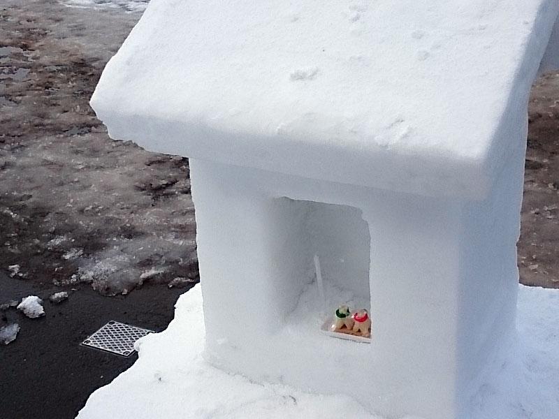 町中にある雪でできた小さいお堂に、しんこ細工の犬っこがいる
