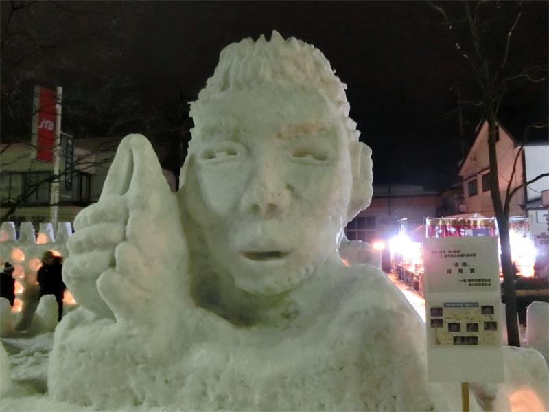 夜、屋台の光に照らされる五郎丸ポーズをしたラグビー日本代表五郎丸選手の雪像