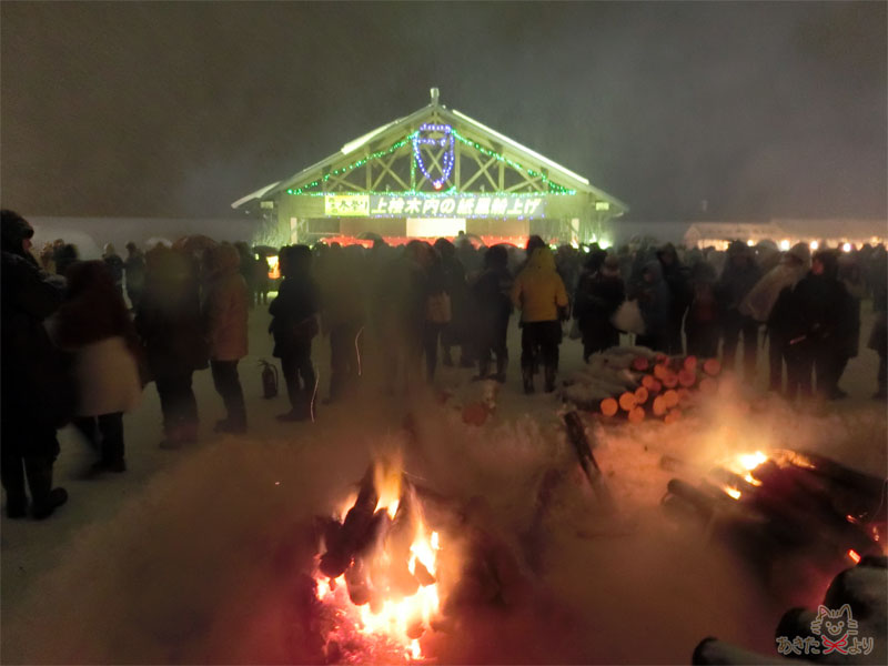 手前には大きめのたき火、奥にあるステージがある