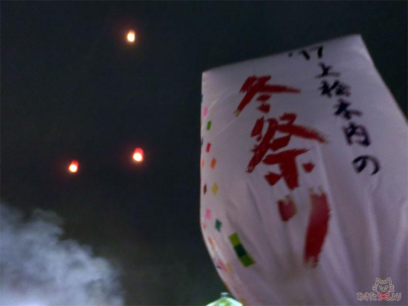 夜空に浮かぶ小さなスカイランタンの灯りと大きな紙風船