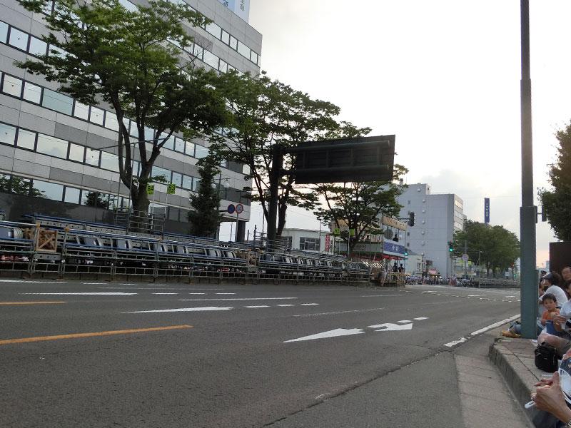 写真左が優良観覧席、写真右側に見えるのが歩道、歩道が少しくぼんでいるのはバス停のため。