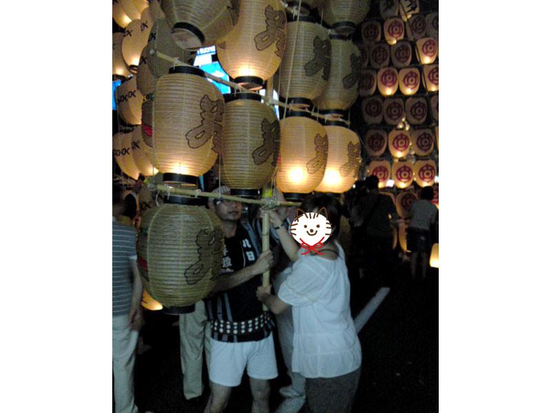 竿燈は伸ばした竿をとって下に下げていて、提灯を背景に差し手の人と写真を撮っている様子