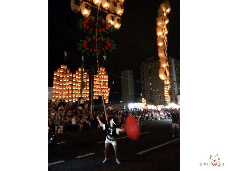 竿燈を上げながら傘を開くパフォーマンスをする人