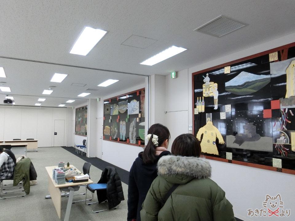 秋田の行事などが描かれた大きな漆のパネルが展示されている体験教室の壁
