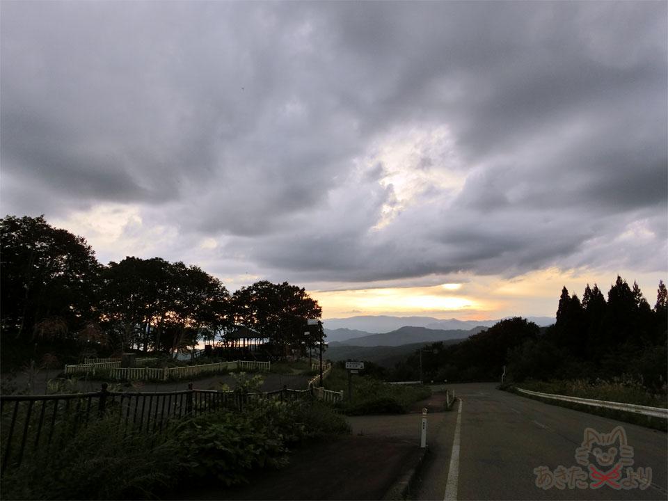 下り坂の道の上から黒森展望台と田沢湖が良く見える