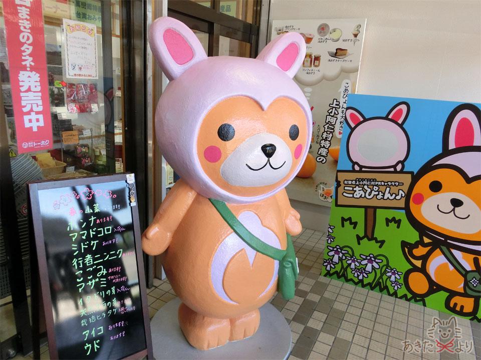 『上小阿仁村物産センター』入り口に、上小阿仁村のPRキャラクター『こあぴょん』とその顔出しパネル、販売している山菜の名前がたくさん書かれた黒板がある