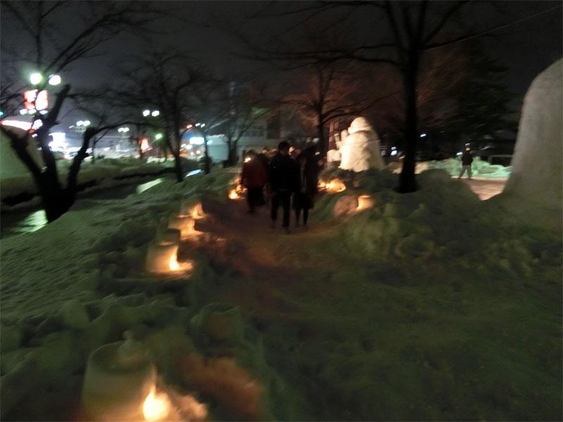 夜、体験で作ったバケツ型のミニかまくらに火が灯っている様子
