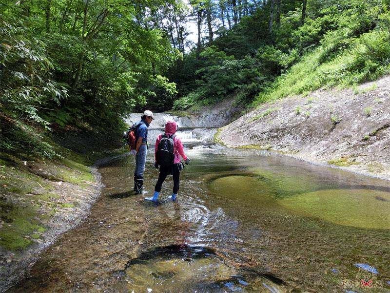 川の中に二人の人が立っていて、小さいおう穴や滝がある様子