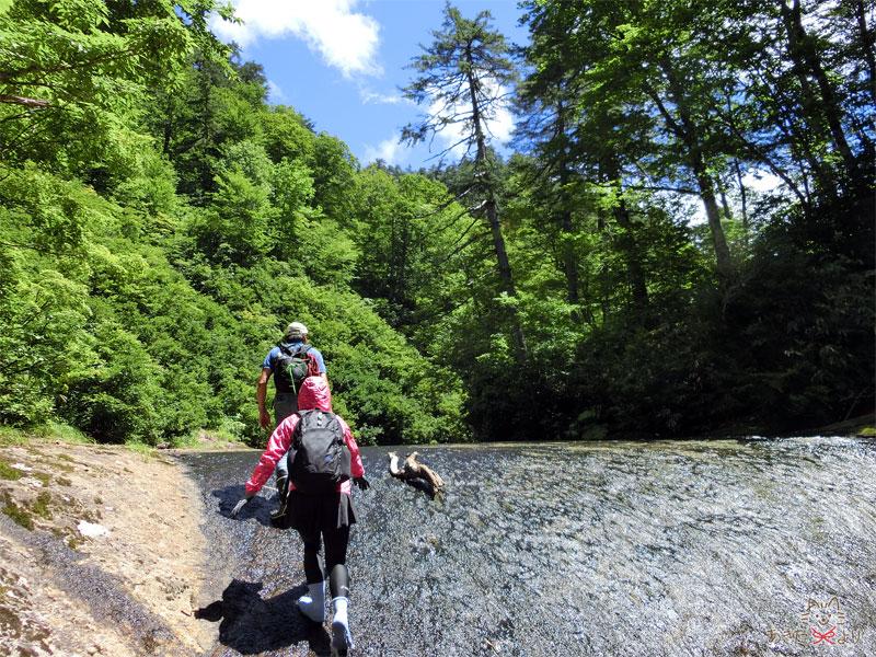 なだらかな滝のように水が流れる岩盤の坂を上る様子