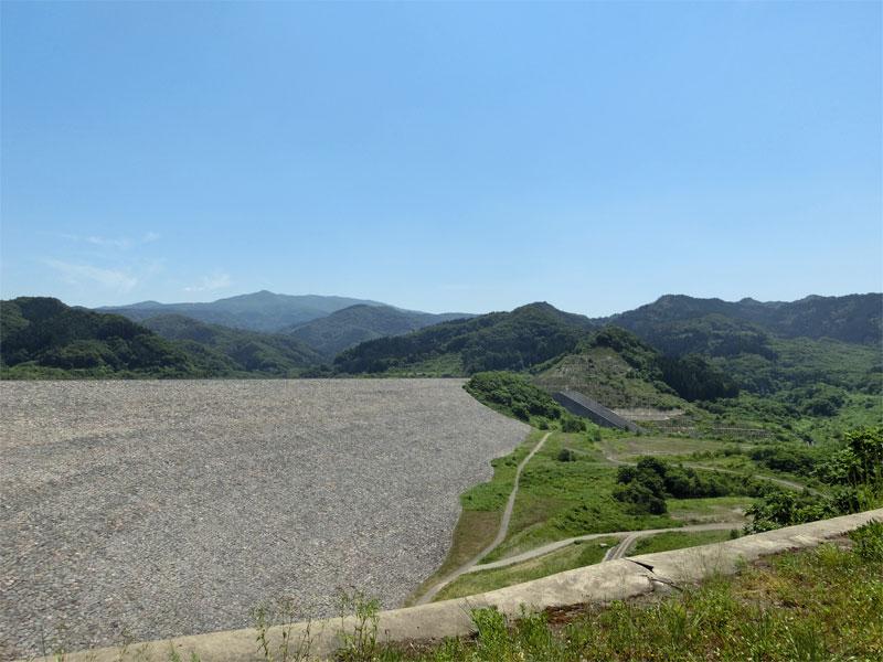 晴れた空、たくさんの岩が積み上がる森吉山ダムの側面