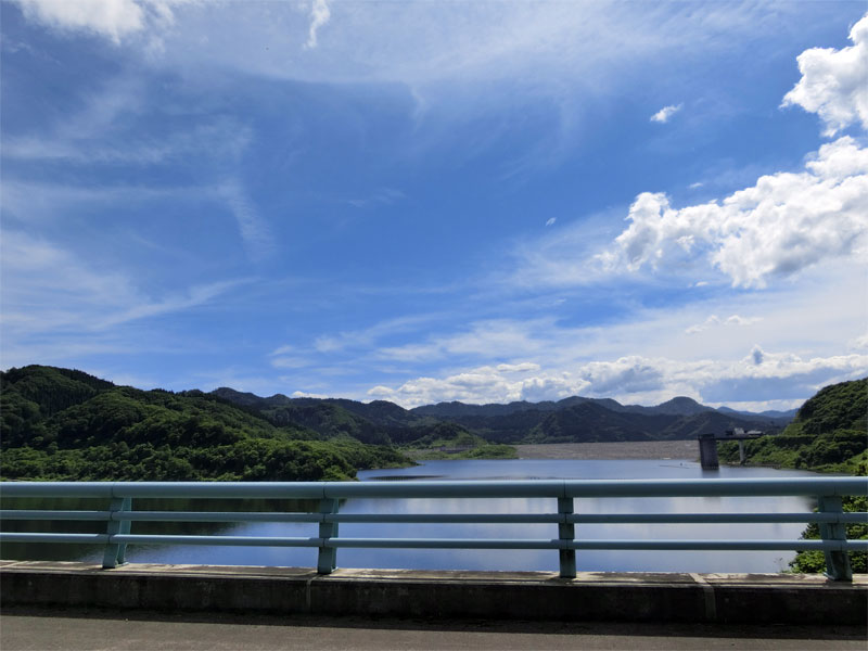 青空の下、橋の上からから見えるダム湖の様子