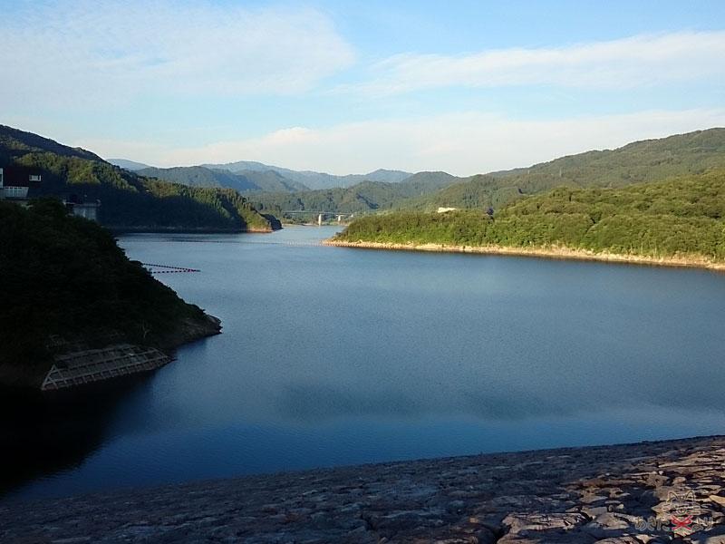 森吉山ダムの上から見たダム湖。写真左には『喫茶ねもりだ』がある広報館が見える。
