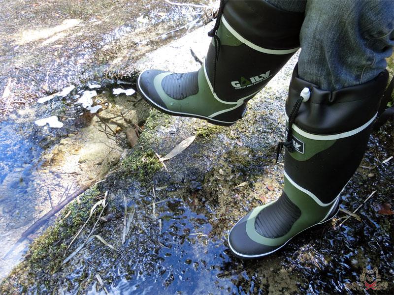 川の上の流木に腰掛け、長靴を履いた足を組んでいる様子