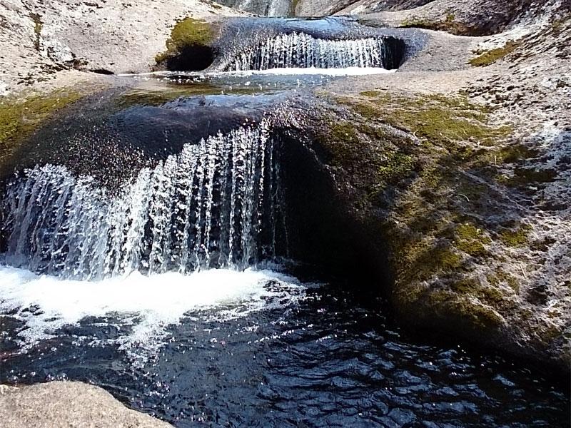 小さい滝が段になって流れていて、黒くて深そうな滝壺がある