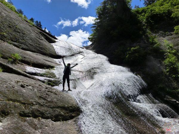ウサギ滝の真ん中あたりで両手を広げて立っている人の様子