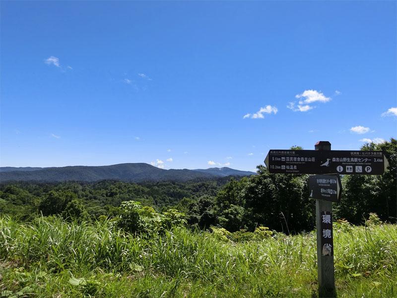 青空の下に見える山々、写真中央には白くくぼんだように見える秋田焼山が映っている