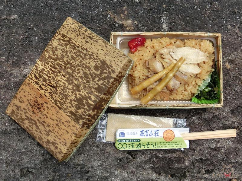 森吉山荘で作ってくれる比内地鶏弁当が、取ったふたと森吉山荘の箸と一緒に岩の上に置かれている様子