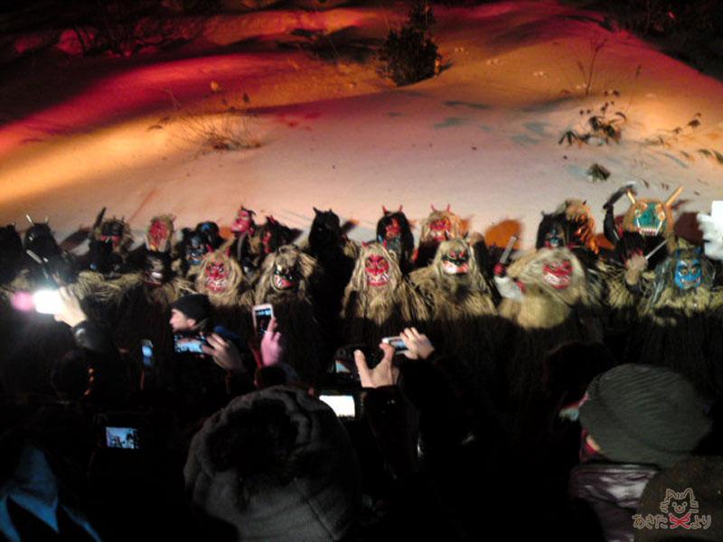夜、雪山の下になまはげが並び、観客が写真を撮っている様子
