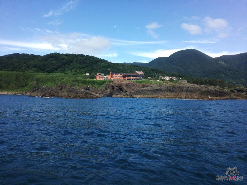 赤い建物が『男鹿桜島リゾート HOTELきららか』。小さく見えるがけっこう大きいホテルで、崖の上に建っている。