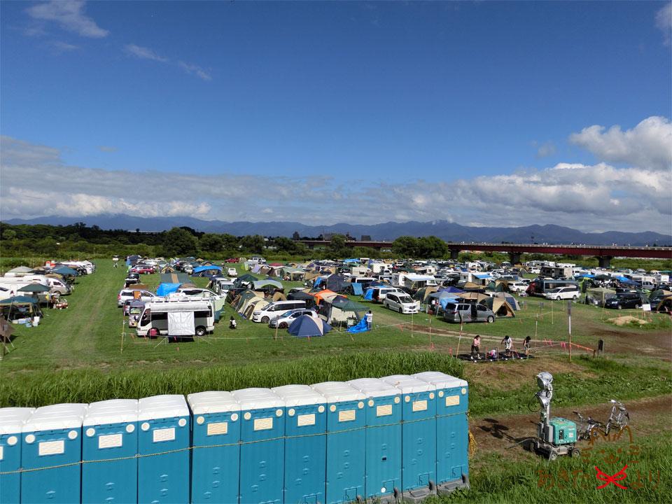水や仮設トイレも設置されている河川敷のテント設営許可駐車場の様子