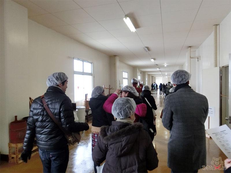 爛漫の廊下で頭にシャワーキャップのような帽子をかぶっている人たちの様子