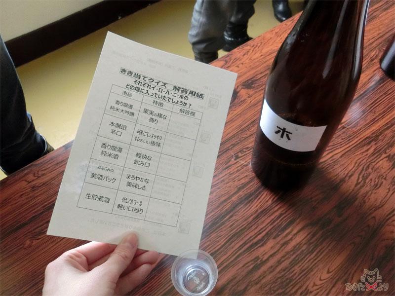 利き酒クイズの紙を持った手とテーブルの上にホとラベルのある酒瓶がある様子
