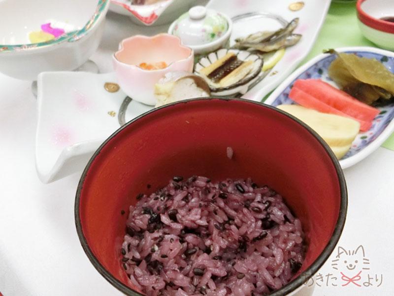 古代米を混ぜた赤いごはんが食卓に上っている様子。