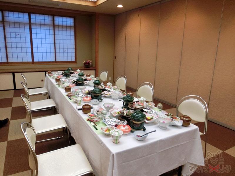 、大きい部屋を仕切った会場にテーブルと椅子があり、テーブルの上にはたくさんの料理が並ぶ