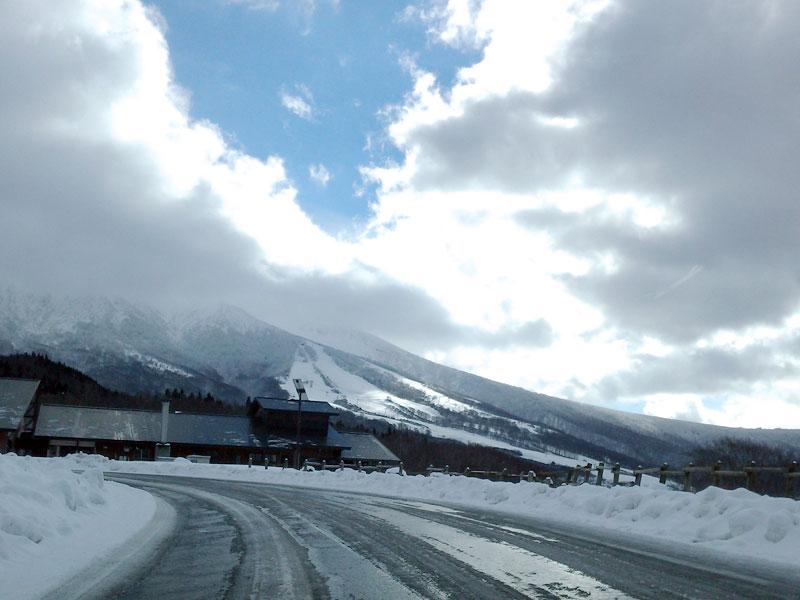 車道にはほとんど雪がなく、周りや山には雪が積もっている様子