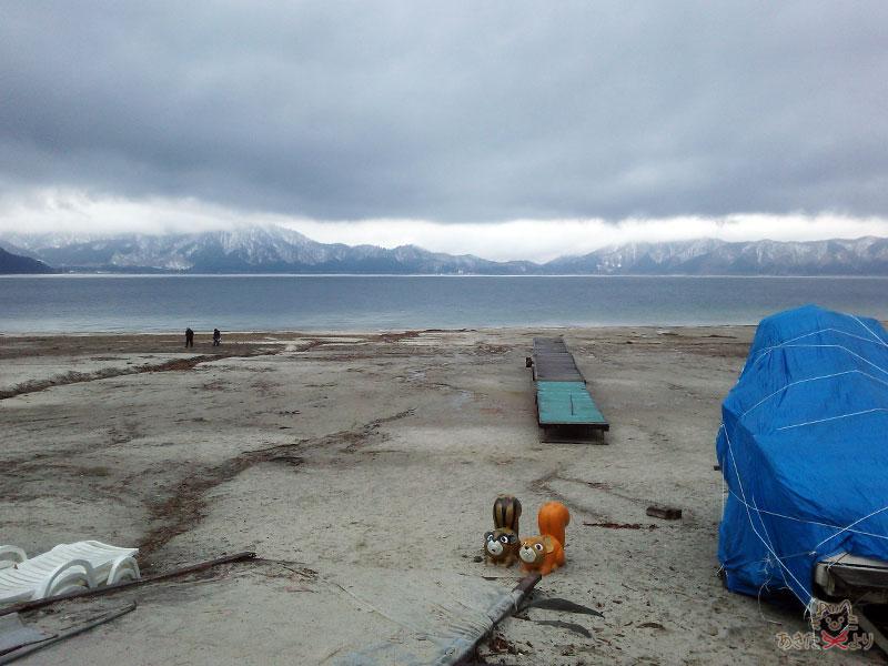 田沢湖の周辺は積雪がないが、見える山々は雪化粧されている様子