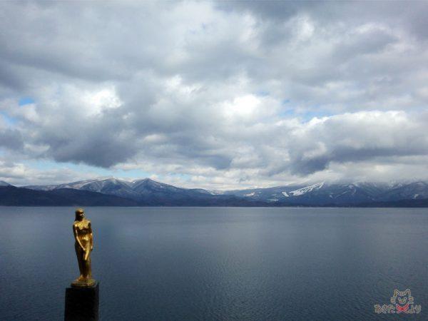 金色のたつこ像と田沢湖、奥に雪化粧されたやみゃやまが見える