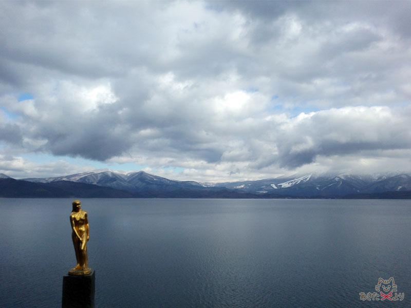 たつ子像と田沢湖、雪化粧された山々の様子