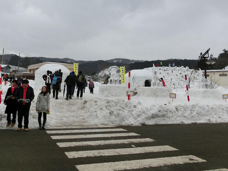 由利高原鉄道矢島駅前の広場にはかまくらや大きな雪山すべり台などが出て子供たちが楽しそうに遊んでいる。