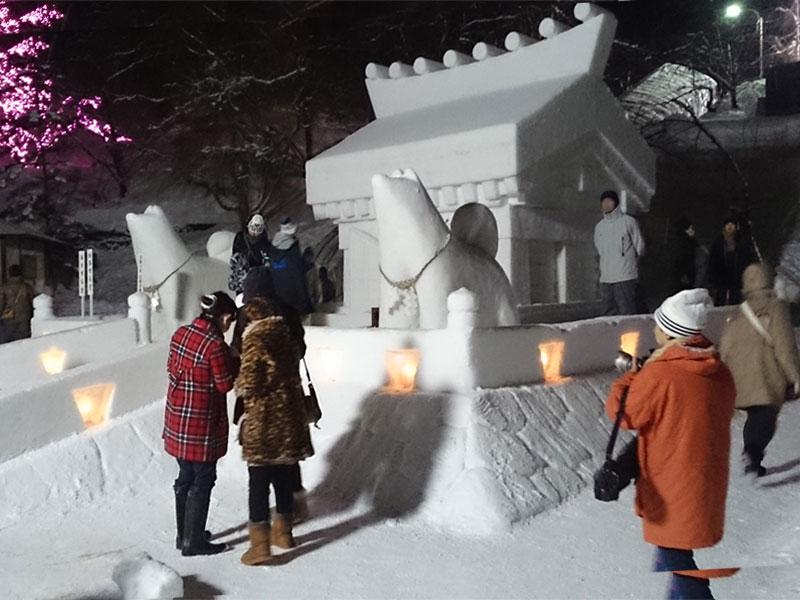 夜、犬っこの雪像と大きい雪のお堂っこの周りに人がいる様子