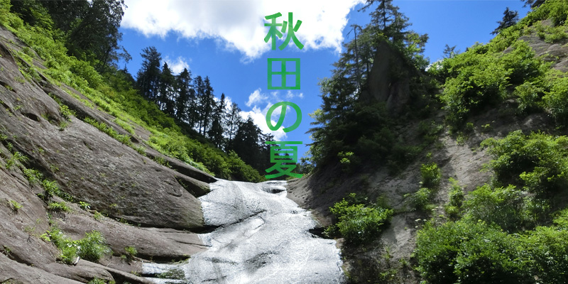 青空の下、中央には桃洞の滝、両脇には新緑がまぶしい